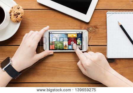 technology, business, people and media concept - close up of woman with news application on smartphone screen and coffee cup on wooden table