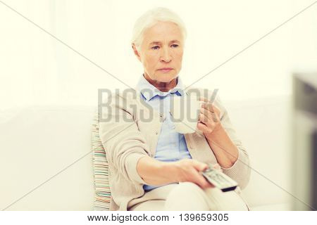 technology, television, age and people concept - senior woman watching tv, drinking tea and changing channels by remote control at home