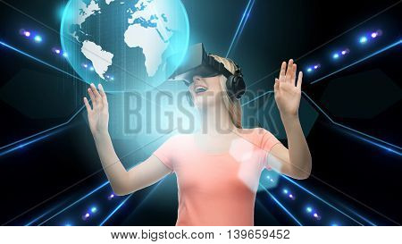 technology, virtual reality, cyberspace and people concept - happy young woman with virtual reality headset or 3d glasses looking at earth hologram over black background and lights