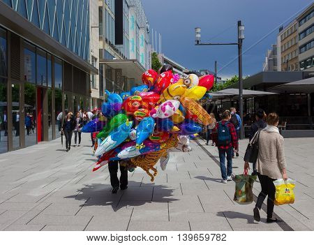 Frankfurt, Germany - June 15, 2016: The dealer of colorful balloons walking along the Zeil in Midday in Frankfurt, Germany. Since the 19th century it is of the most famous and busiest shopping streets in Germany.