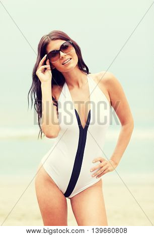 summer vacation, tourism, travel, holidays and people concept - smiling young woman in swimsuit with sunglasses on beach