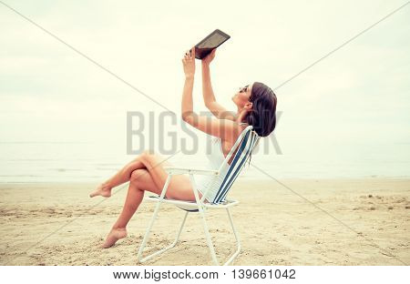 summer vacation, tourism, travel, holidays and people concept - smiling young woman with tablet pc computer sitting folding chair and taking selfie on beach