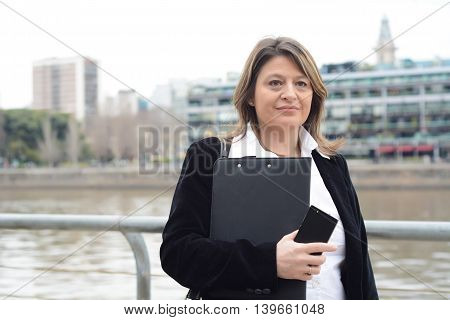 Portrait of business woman holding clipboard and smartphone. Outdoors.