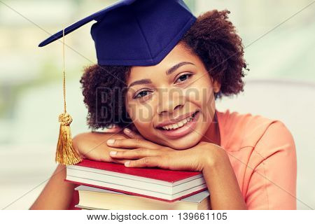 education, school, knowledge, graduation and people concept - happy smiling african american student girl in bachelor cap with books sitting at table and dreaming at home