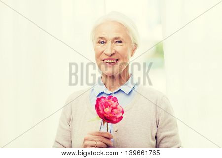 age, holidays and people concept - happy smiling senior woman with flower at home
