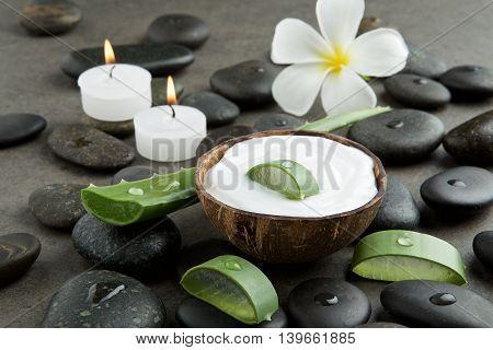 Spa Concept. Slice Aloe Vera On White Cream In Coconut Shell With Stone, Plumeria, Candle Light Back