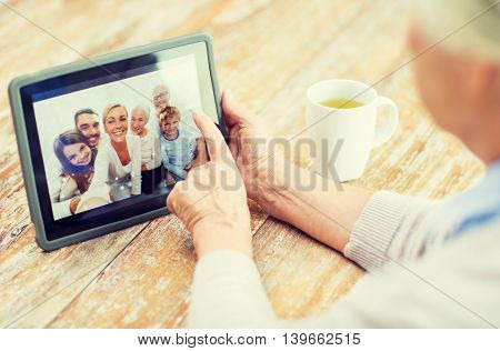 technology, age, memories and people concept - happy senior woman with tablet pc computer viewing family photo album at home