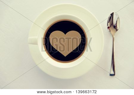 drinks, morning, love and valentines day concept - cup of black coffee with heart shape symbol on surface, spoon and saucer on table