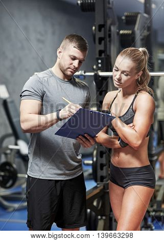 fitness, sport, exercising and diet concept - young woman and personal trainer with clipboard writing exercise plan in gym