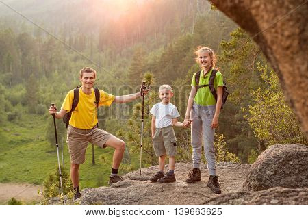 Father and two children with backpacks on beautiful scene of nature