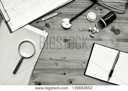 Assorted office supplies on doctor's desk. General medical practitioner workspace as copy space monochromatic image top view.