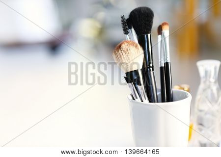Cosmetic brushes in cup on light blurred background