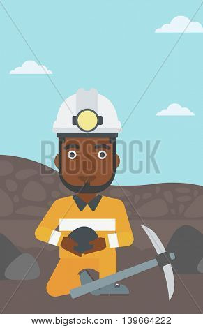 An african-american miner in hard hat sitting with coal in hands and a pickaxe on the background of coal mine. Vector flat design illustration. Vertical layout.
