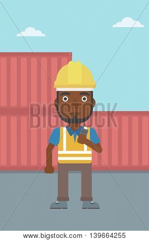 An african-american port worker talking on wireless radio. Port worker standing on cargo containers background. Man using wireless radio. Vector flat design illustration. Vertical layout.