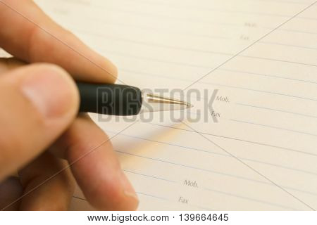 Hand writing mobile phone number in business agenda close up with selective focus