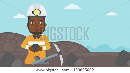 An african-american miner in hard hat sitting with coal in hands and a pickaxe on the background of coal mine. Vector flat design illustration. Horizontal layout.