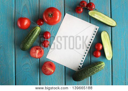 Sheet and composition of vegetables on blue wooden desk. Tomato, cucumber. Top view.