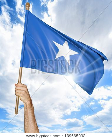 Person's hand holding the Somalian national flag and waving it in the sky, 3D rendering