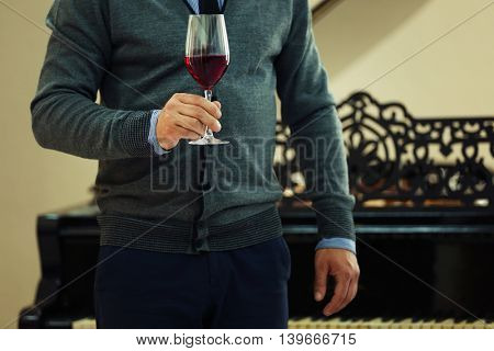 Man holding glass of red wine in hand