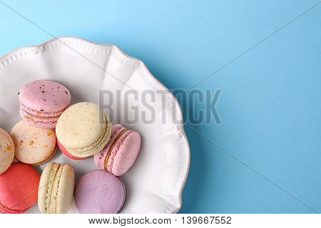 Tasty colorful macaroons in white plate on light blue background
