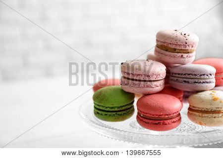 Colorful tasty macaroons in glass stand on light background
