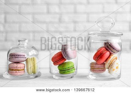 Colorful tasty macaroons in glass jars on light brick wall background