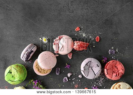 Different colorful tasty macaroons on gray background