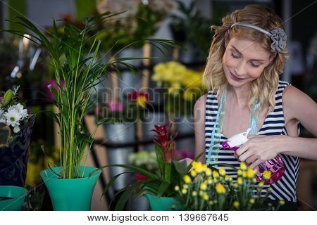Female florist spraying water on flowers in the flower shop
