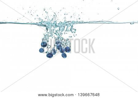 Fresh blueberries falling in water on white background