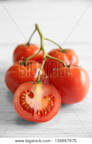 Bunch of red juicy tomatoes on light wooden background