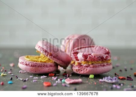 Pink broken tasty macaroons on gray table