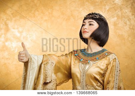 Thumbs up. Glamorous closeup portrait of beautiful sexy stylish brunette young woman model with bright makeup with gold jewelery. Cleopatra