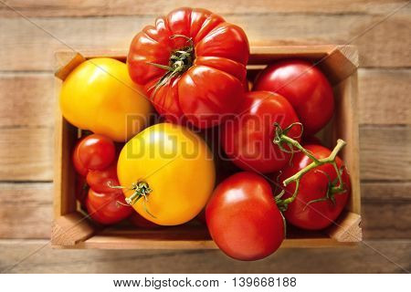 Different tomatoes in box on wooden background