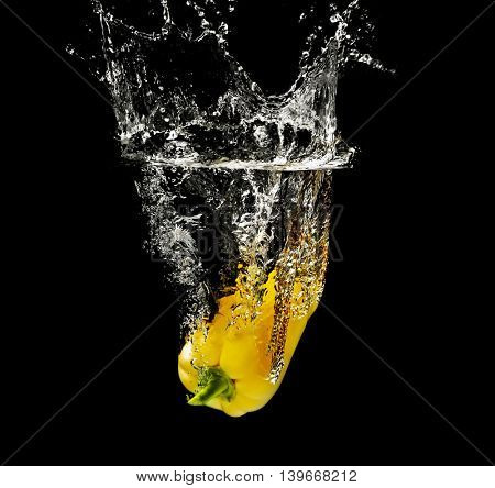 Fresh yellow pepper falling in water on dark background