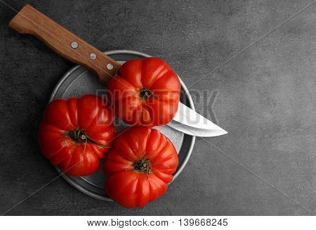 Red juicy tomatoes and knife in plate on dark background