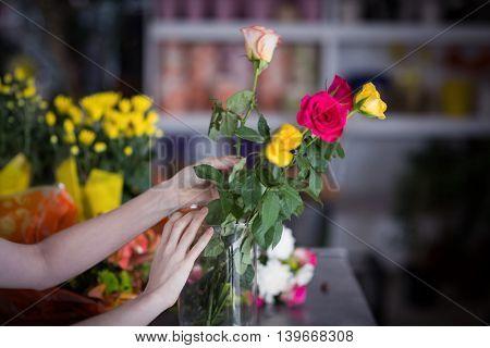 Female florist arranging flower bouquet in vase at flower shop