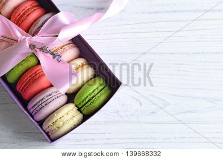 Different colorful macaroons in gift box on light wooden background