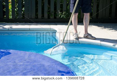 A man with a net cleaning the last part of the swimming pool before the cover goes on