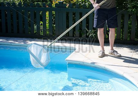 Man with a net cleaning a swimming pool