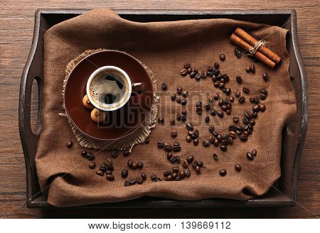 Cup of coffee with beans on wooden tray