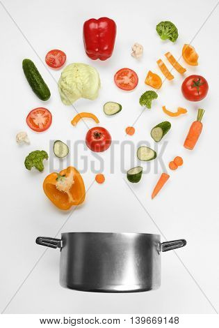 Fresh vegetables falling into a casserole pot on white background