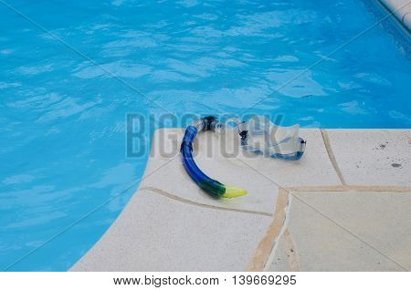 Snorkel and mask lying on the tiles at the edge of a swimming pool