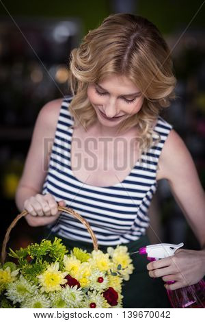 Smiling female florist spraying water on flowers in flower shop