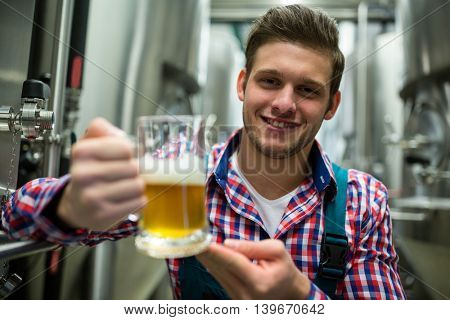 Portrait of brewer holding a glass of pint beer