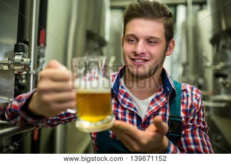 Brewer holding a glass of pint beer