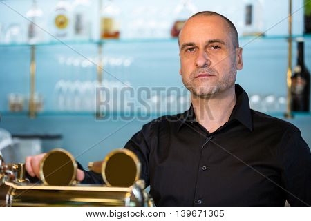 Portrait of bar tender standing at bar counter
