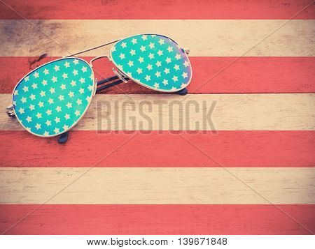 mirror glasses with star pattern on red striped wooden background vintage filter effect. American flag and 4th of July concept.