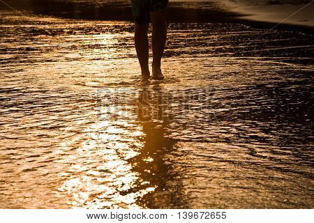 Feed Of Walking Man At The Water In The Beach In Backlight