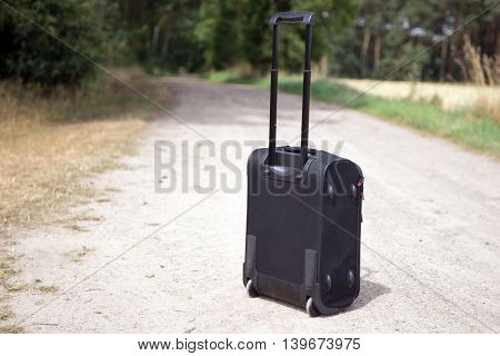 Hand luggage suitcase on the dirt road