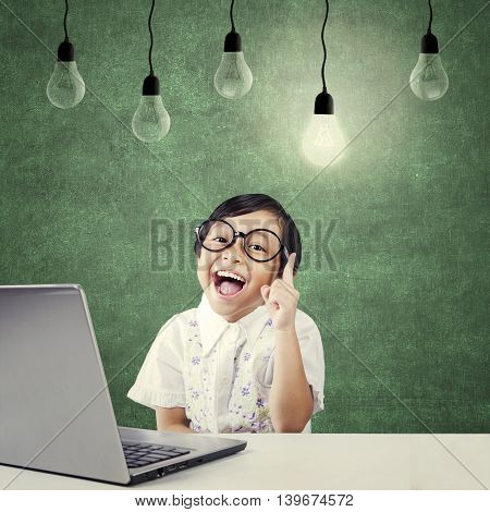 Portrait of clever kindergarten student with laptop on the table pointing at bright light bulb